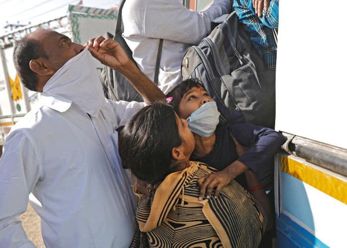 На окраине Дели 29 марта: женщина с дочерью пытаются сесть в переполненный автобус, чтобы уехать домой в деревню © Reuter