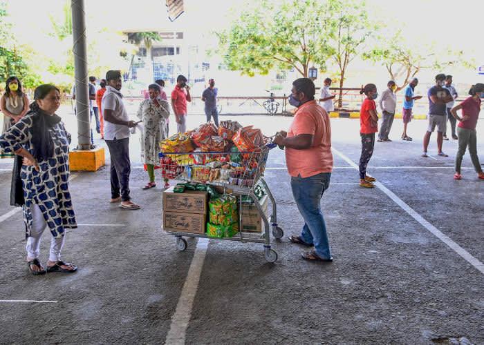 Люди стоят в очередях, чтобы купить продукты в супермаркете. Бангалор © Getty Images