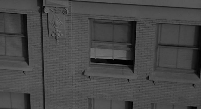 Камера заглядывает в одно из окон многоэтажных зданий