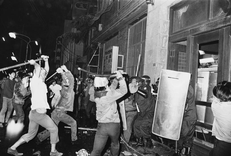 Радикальные студенты-демонстранты размахивают железными прутьями в сторону группы силовиков во время нападения на токийск