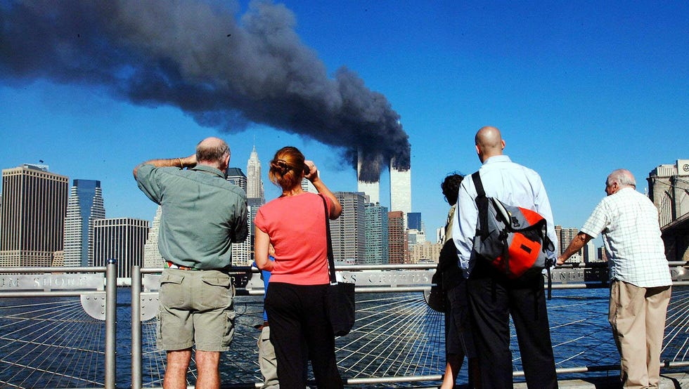 Прохожие смотрят на охваченные пожаром башни-близнецы