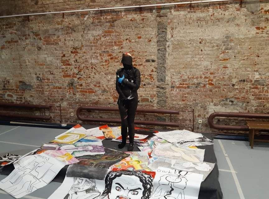 На фотографии изображена фигура художницы, которая вся обмотана черным бинтом. Она прикрывает руками те части тела, где у