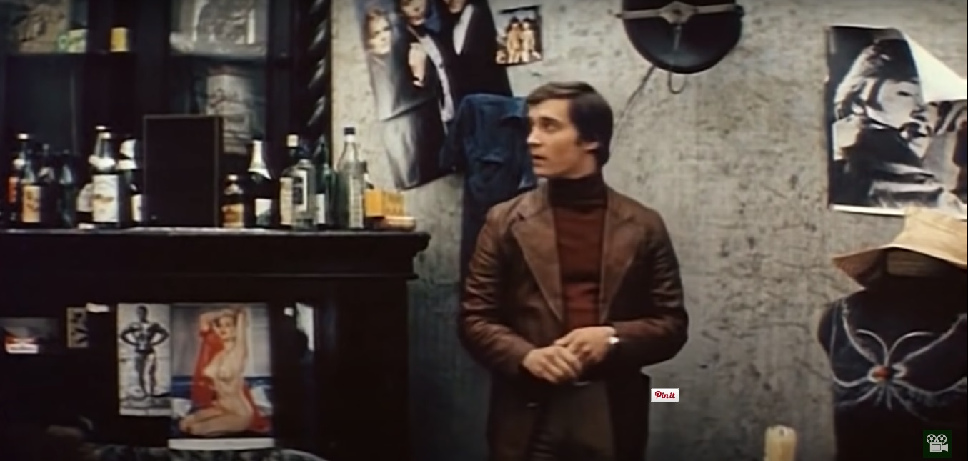 Валентино, он же Валентин Росляков (Евгений Герасимов) рассматривает типичный богемный интерьер: свечи, постеры, много бу