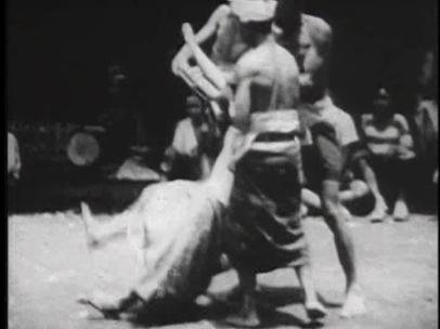 [11:04] Эта женщина отбивается, пока у нее отбирают кинжал. На фоне видны мужчины, тоже в состоянии транса, и женщины в з