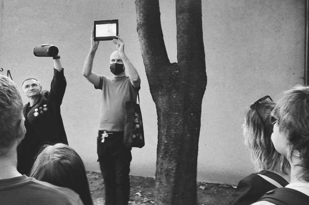 колонка, планшет, режиссёр, актёр спетакля и публика рядом с деревом