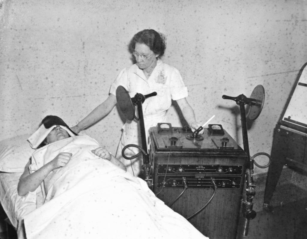 Больница св. Елизаветы. Медсестра c пациентом после сеанса электрошоковой терапии (National Archives RG 418-P-350)
