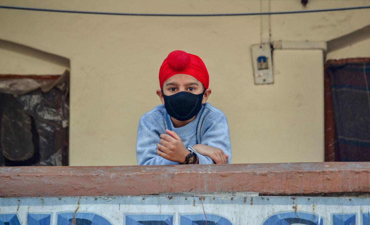Город Сринагар: мальчик в защитной маске осмелился выйти на балкон. В конце марта вгороде зарегистрирован первый умерший
