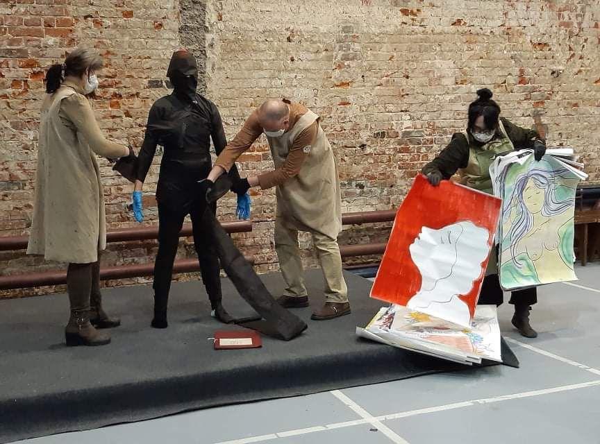 На фотографии изображены художники и художницы в момент перформанса. Их четверо. Трое из них стоят на невысокой черной сц